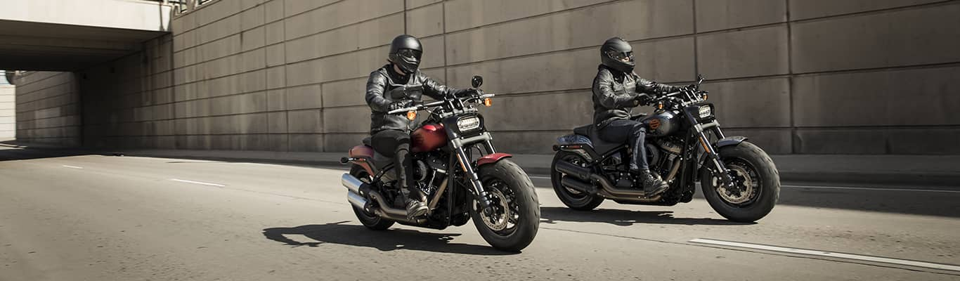 Two people riding Harley-Davidson® motorcycles down street